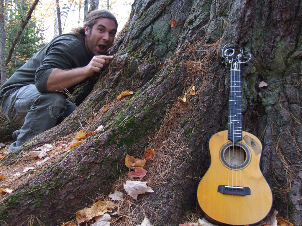 A musician with long hair points excitedly at a tree with a guitar leaning against it