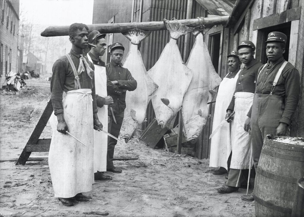 Black chefs pose by three halibut hanging from a rack outside