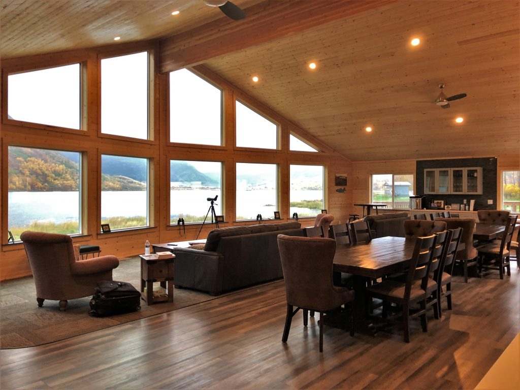 Interior of a wooden lodge with couches and tables and floor to ceiling windows