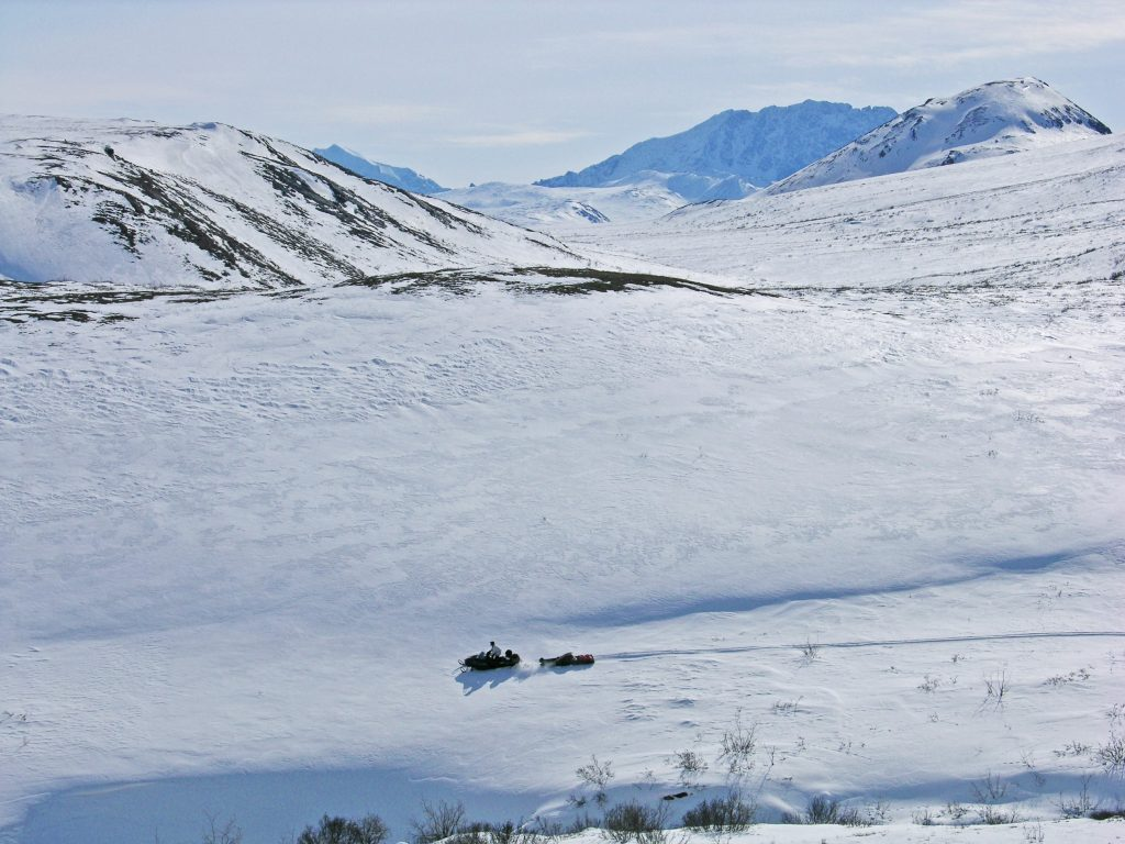 Wide open winter landscape and a small man and snowmobile