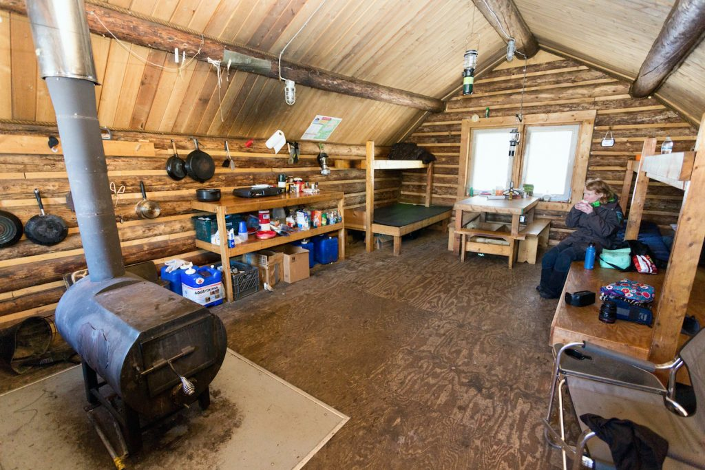 Interior of a public use cabin with stove and supplies