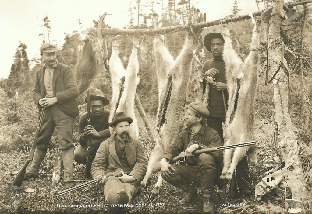 Men pose with rifles and carcasses of three mountain goats