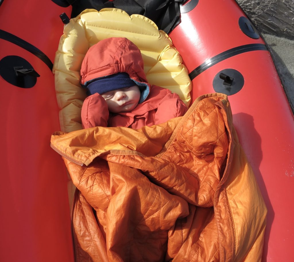 Infant sleeping in a red packraft