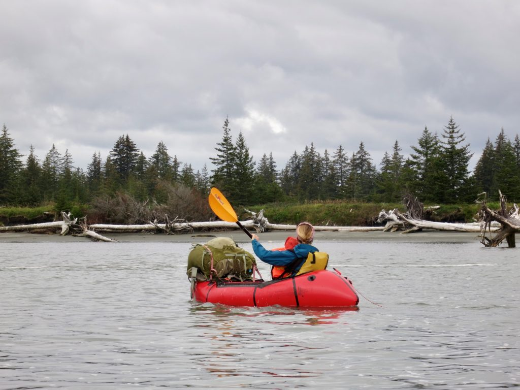 Woman and infant son paddle a packraft along an Alaskan river