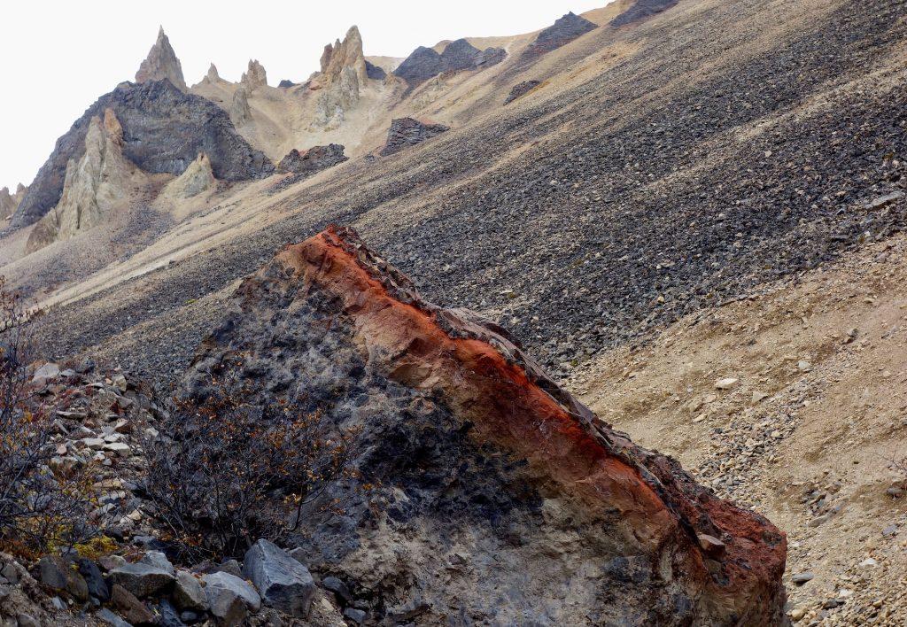 Black boulder with red top. Ridgeline behind