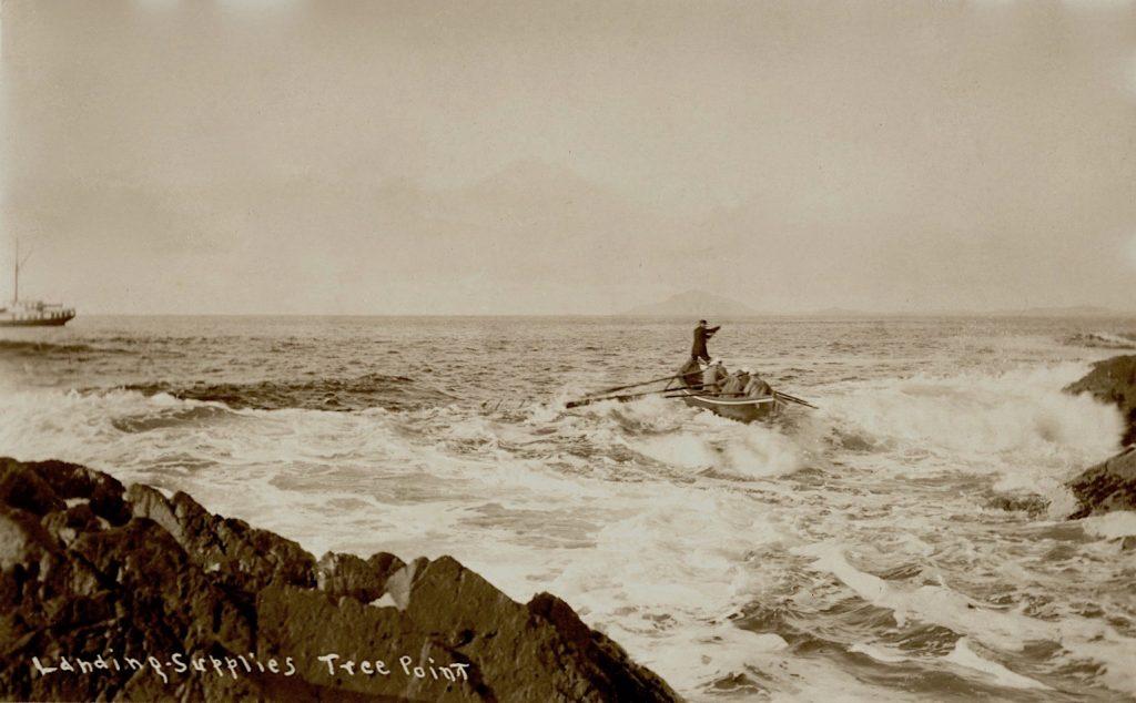 Historic photo of men rowing supplies into a rocky coast