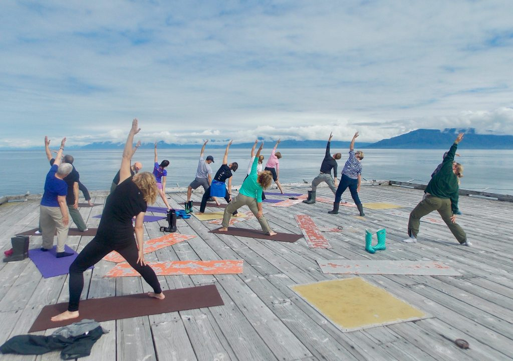 Group yoga on a deck overlooking ocean