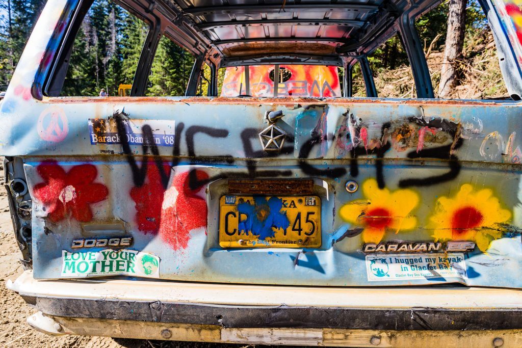The tailgate of a vehicle painted with flower designs and letters