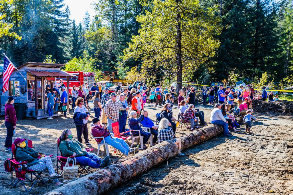 A crowd of people watch on a sunny day from behind logs