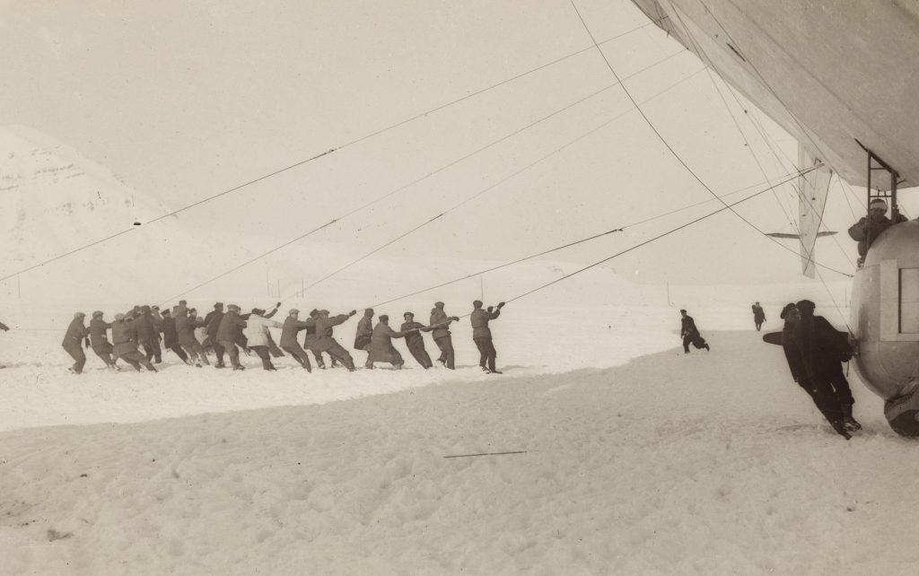 Lines of men pull on ropes securing the Norge to the ground