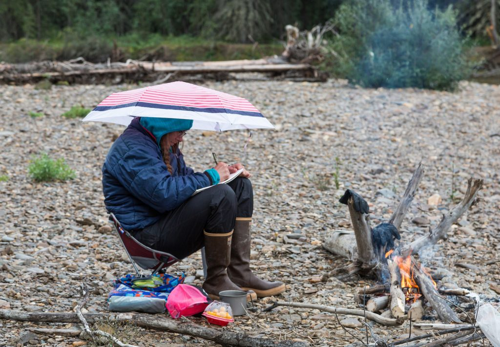 A woman sits under an umbrella in a camp chair by a small campfire and draws on a pad of paper.