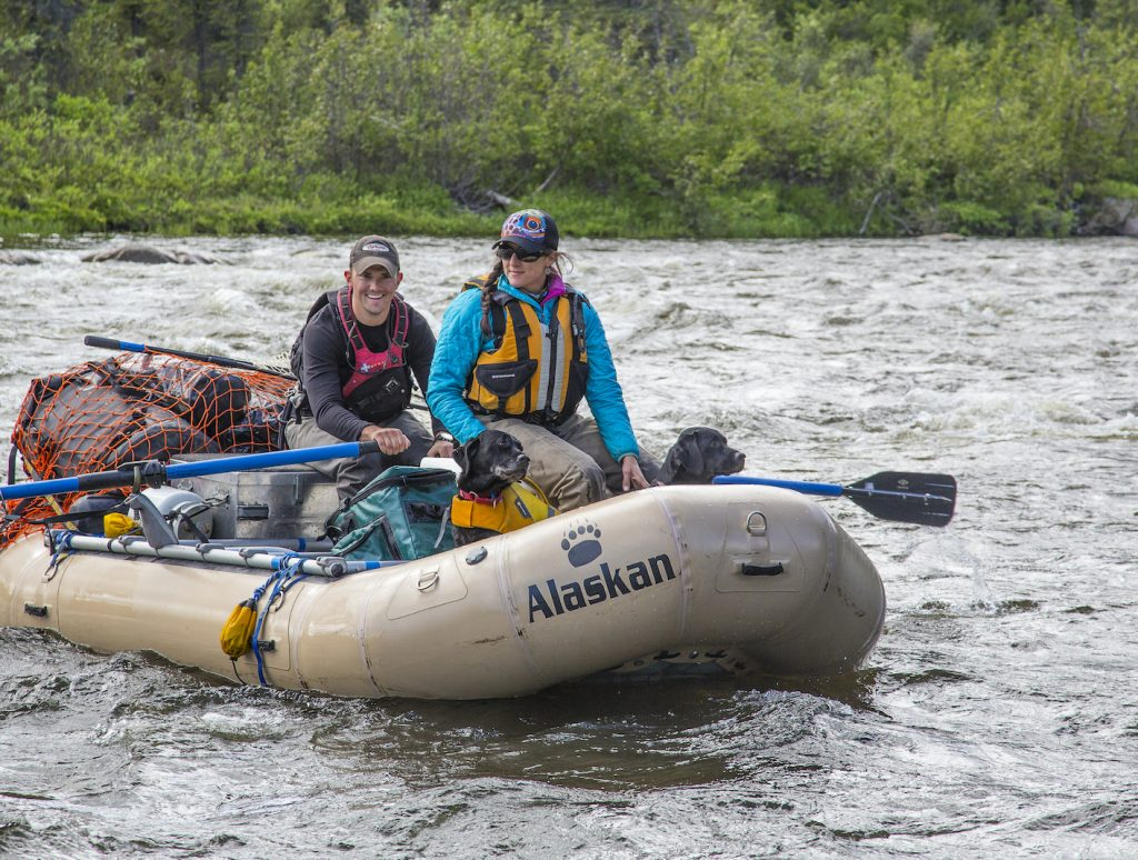 Male and female in a raft with two dogs floating down a river
