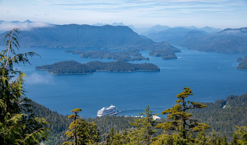 Cruise ship docked along forest coast. View of Inside Passage waters and islands.