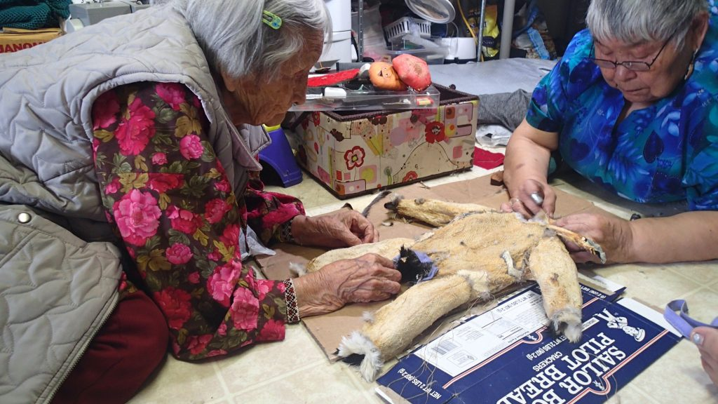Two elderly Alaska Native women sew a small bird skin parka