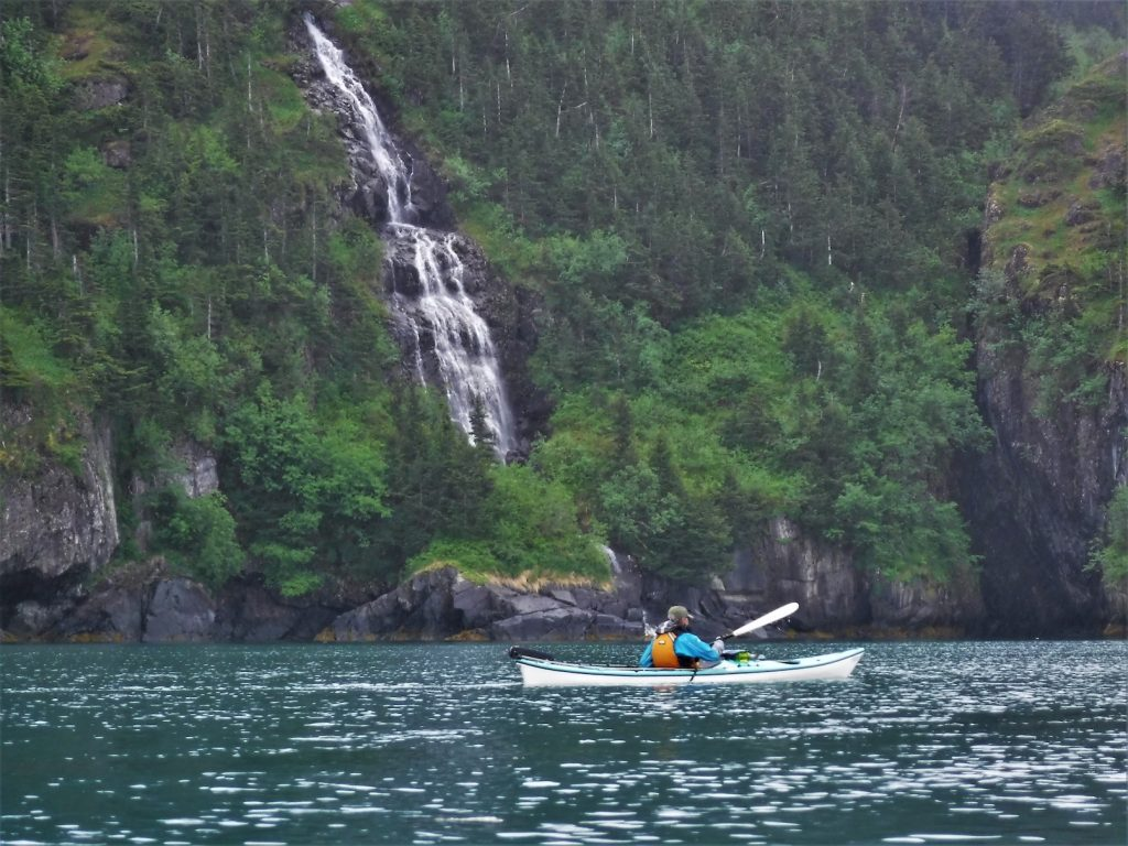 Kayaker paddles past cliffs covered in trees and a waterfall cascading into the ocean