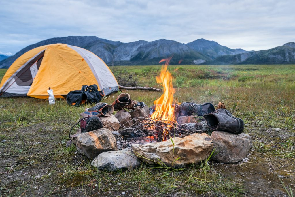 A yellow tent, campfire surrounded by rocks and boots, in a field with mountains behind