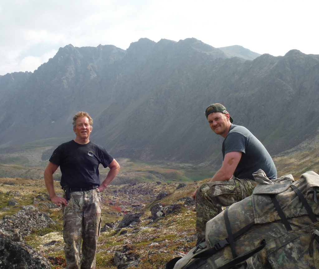 Father stands while son sits on a rock to the right while sheep hunting in the chugach