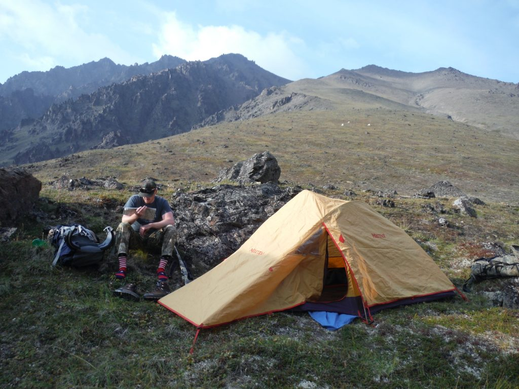 Yellow tent and man sitting nearby in mountainous country