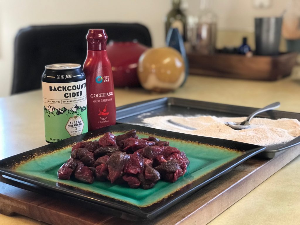 Chunks of caribou on a plate with gochujang sauce and a can of cider