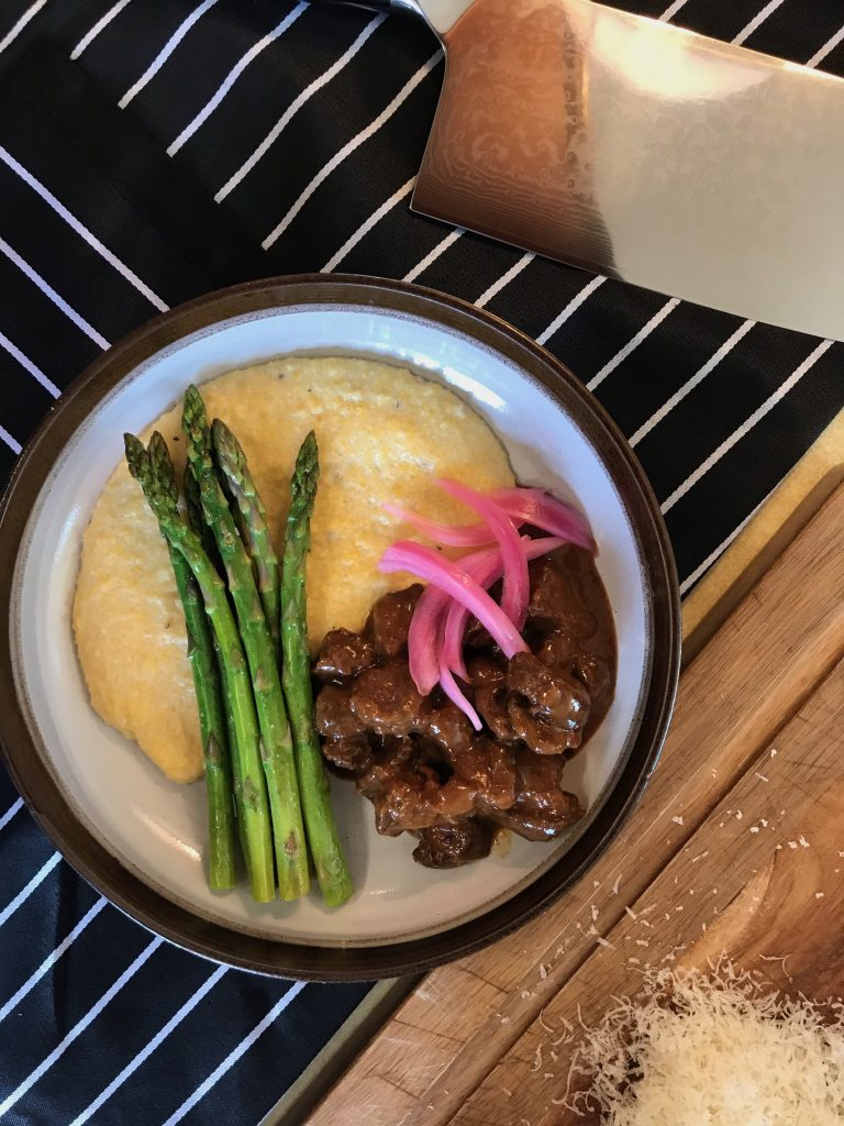 chunks of braised caribou next to pickled onion, asparagus and polenta