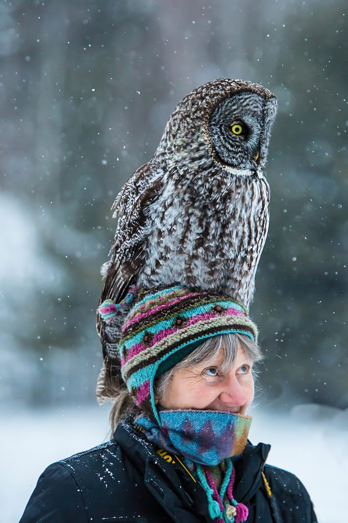 Wildlife photographer Libby Libbey in winter gear with an owl on her head