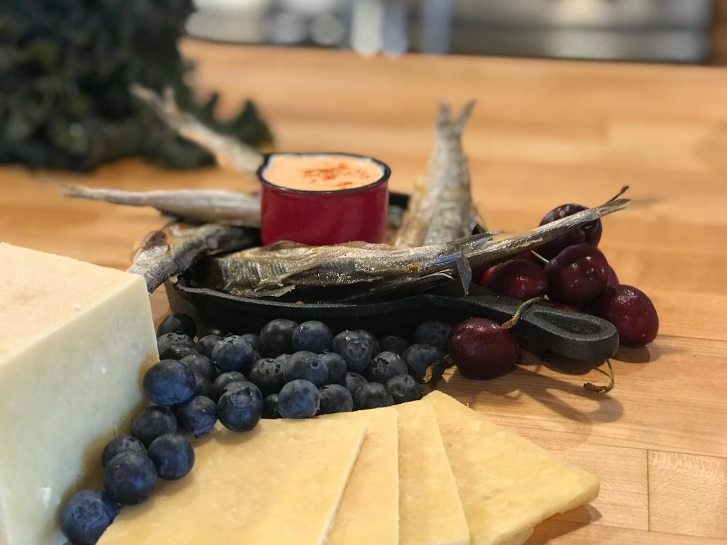 dried small fish spread around red sauce near blueberries and cheese on wood