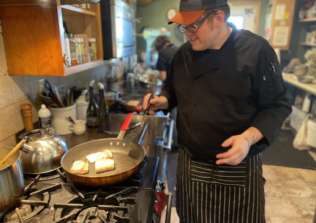 Chef Andrew maxwell in black apron and a ballcap pan sears halibut