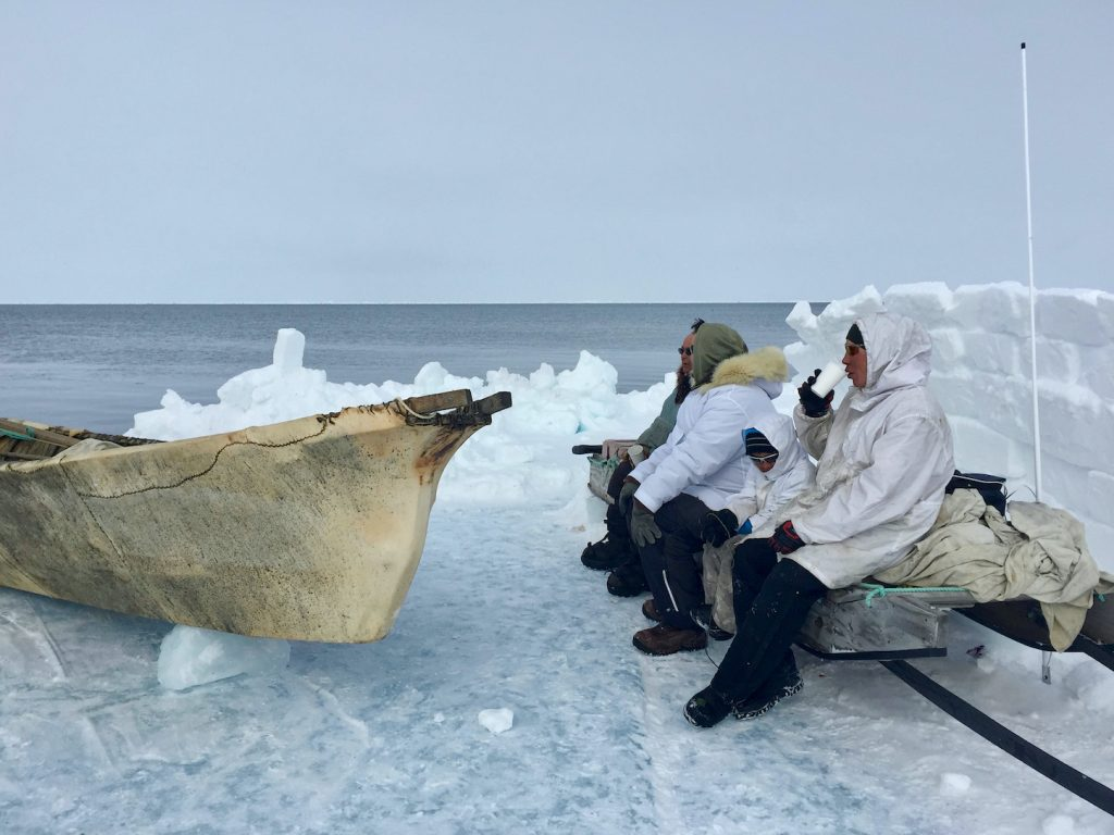 Three men and a child in winter gear sit on a wooden bench beside a whaling boat behind a wall made of snow blocks