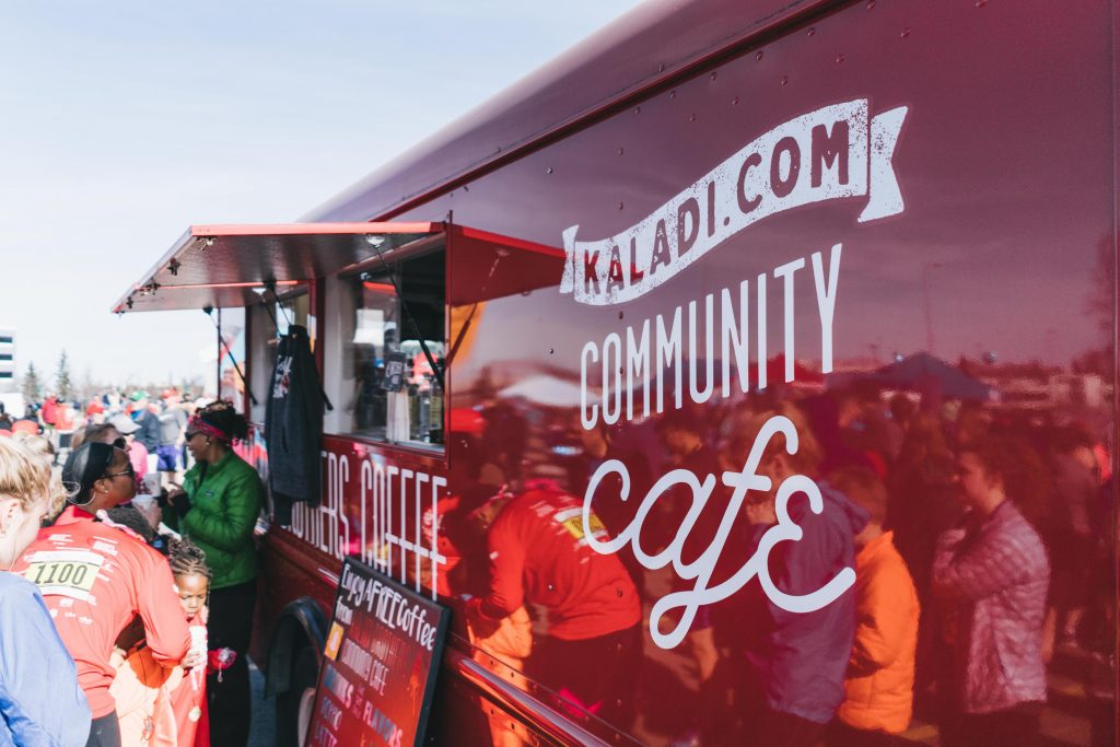 Bright red food truck and workers handing out coffee