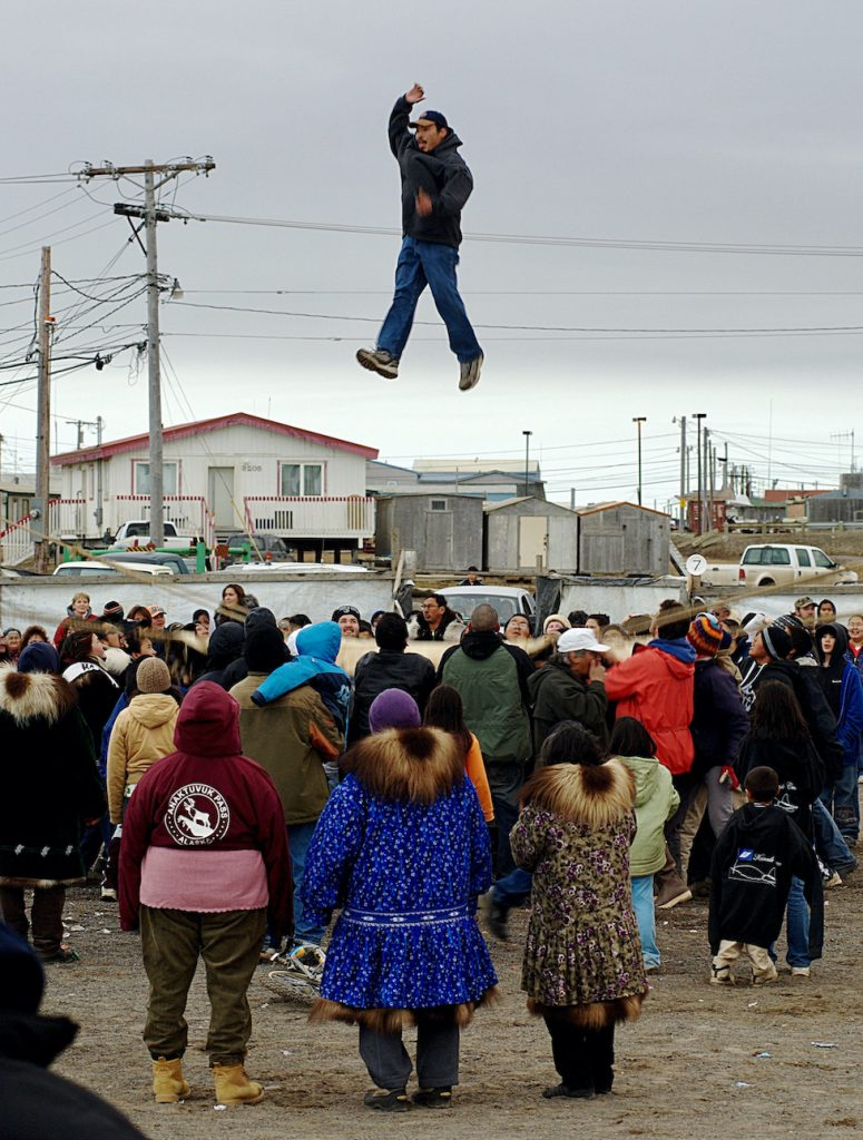 Man is bounced high by a group of people holding a large blanket