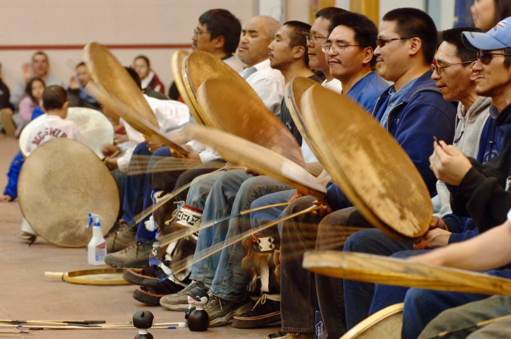 Large group of male drummers use sticks to beat handheld drumheads