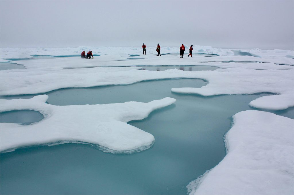 People walk on landscape of ice and melted water ponds