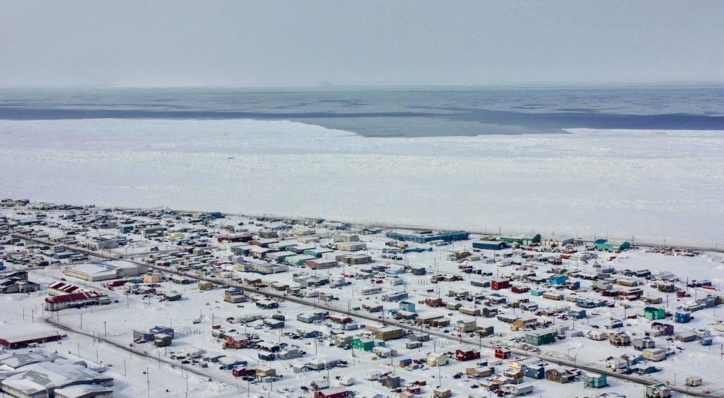 Aerial of homes along coastline and frozen ocean