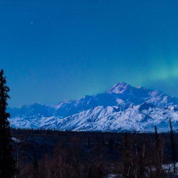Denali basking in moonlight and aurora