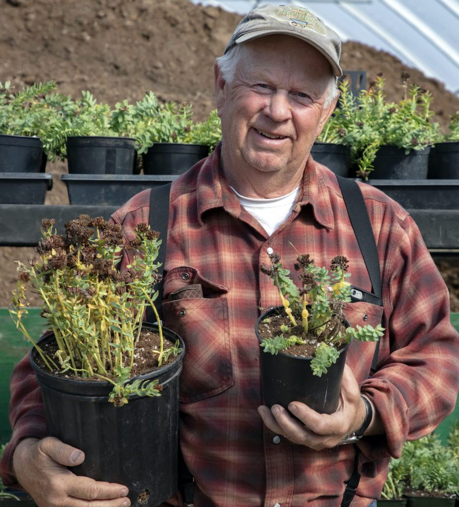 Al Poindexter, an older gentleman in flannel, suspenders, and ballcap, holds potted plants