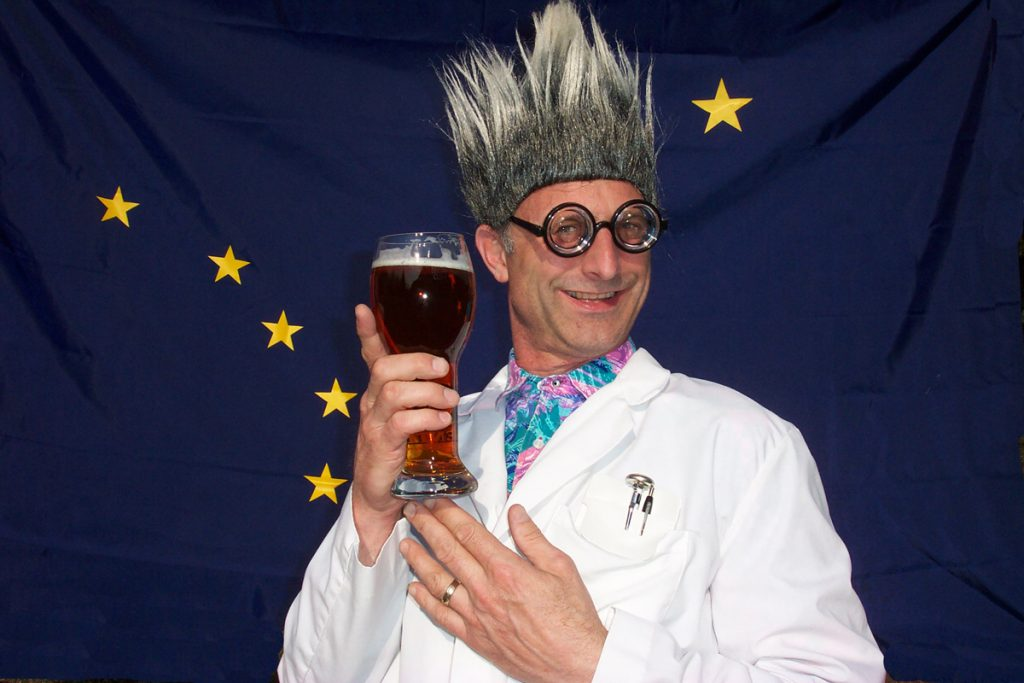 Guy poses in front of an Alaska flag wearing a lab coat, gray wig, and glasses while holding a craft beer