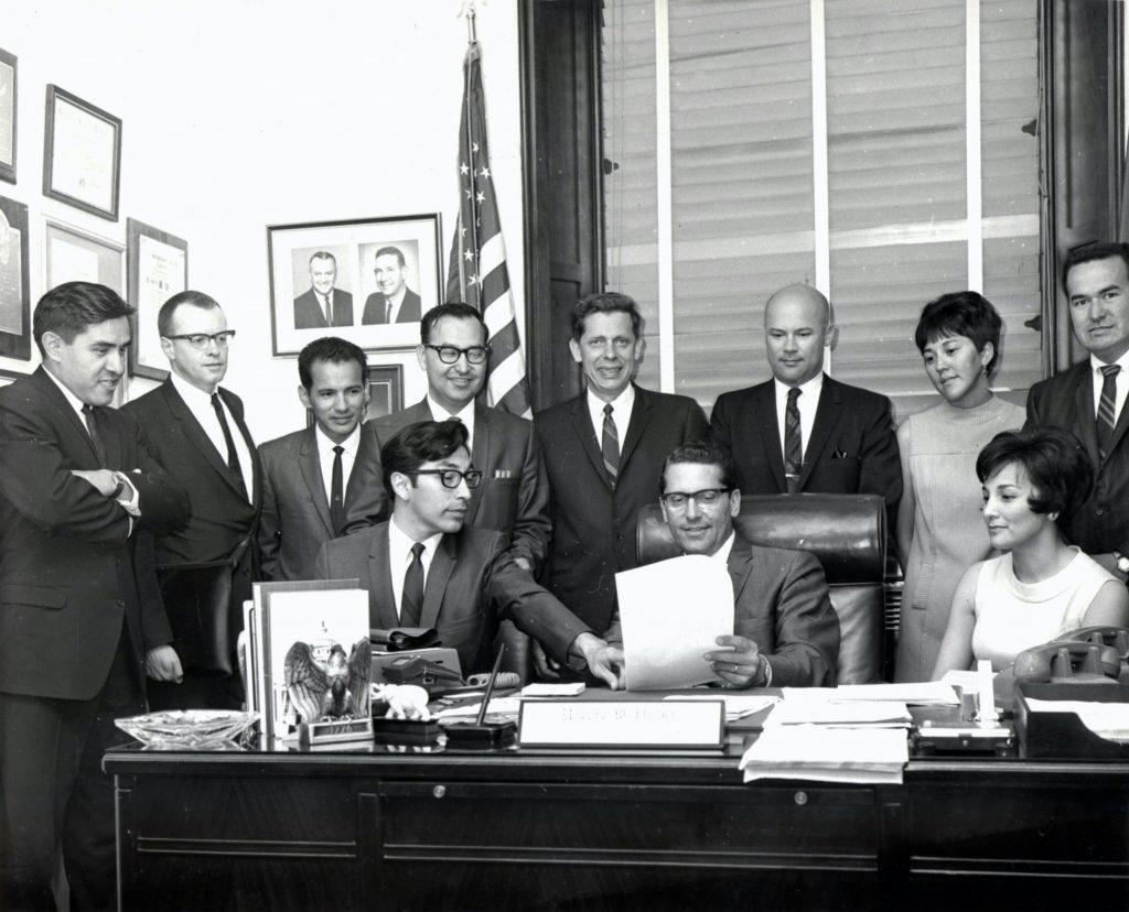 Black and white image of Alaskans around a desk