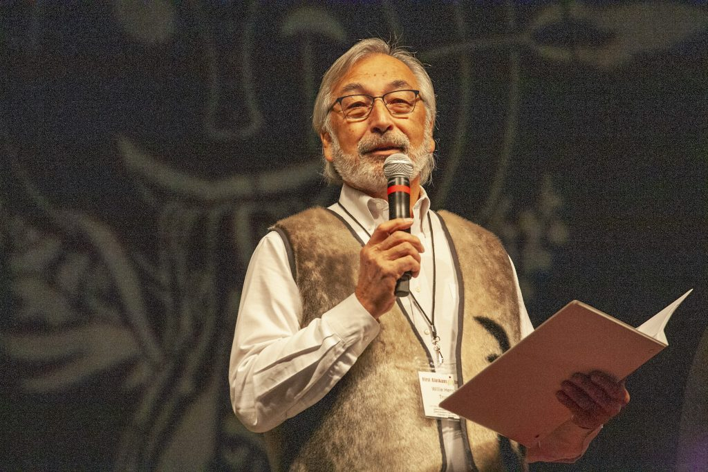Gray-haired Alaska Native man with beard wearing a vest speaking on microphone