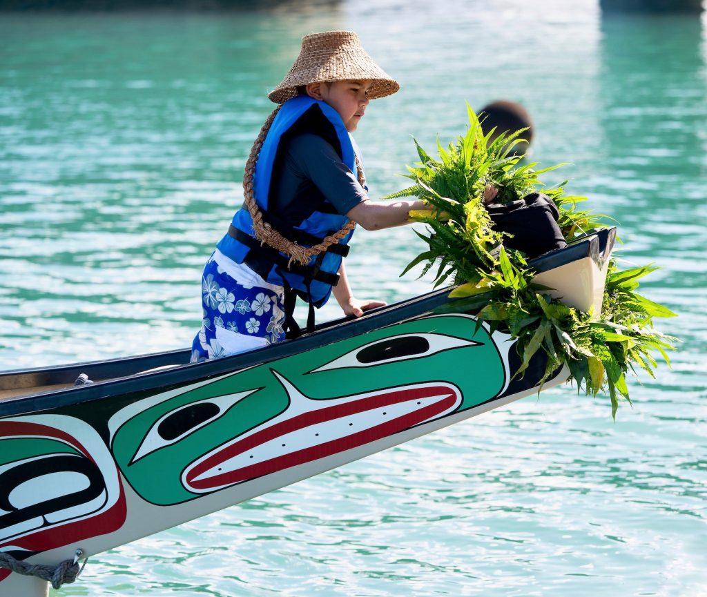 Child places lei on bow of yakutat canoe