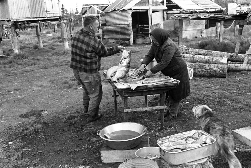 Black and white photo of couple filleting fish on a table
