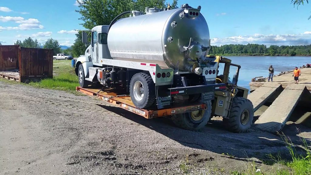 A commercial sewage truck is brought via forklift onto a dirt road by the side of a river