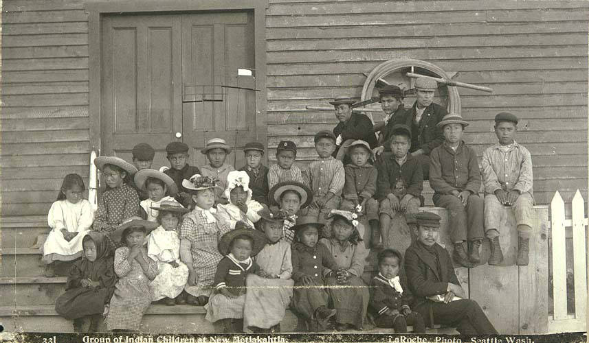black and white photo of children lined up in front of wooden building