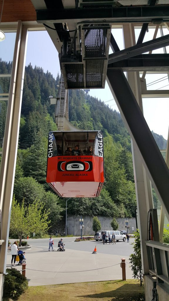 Image of red tram departing station and heading up mountain