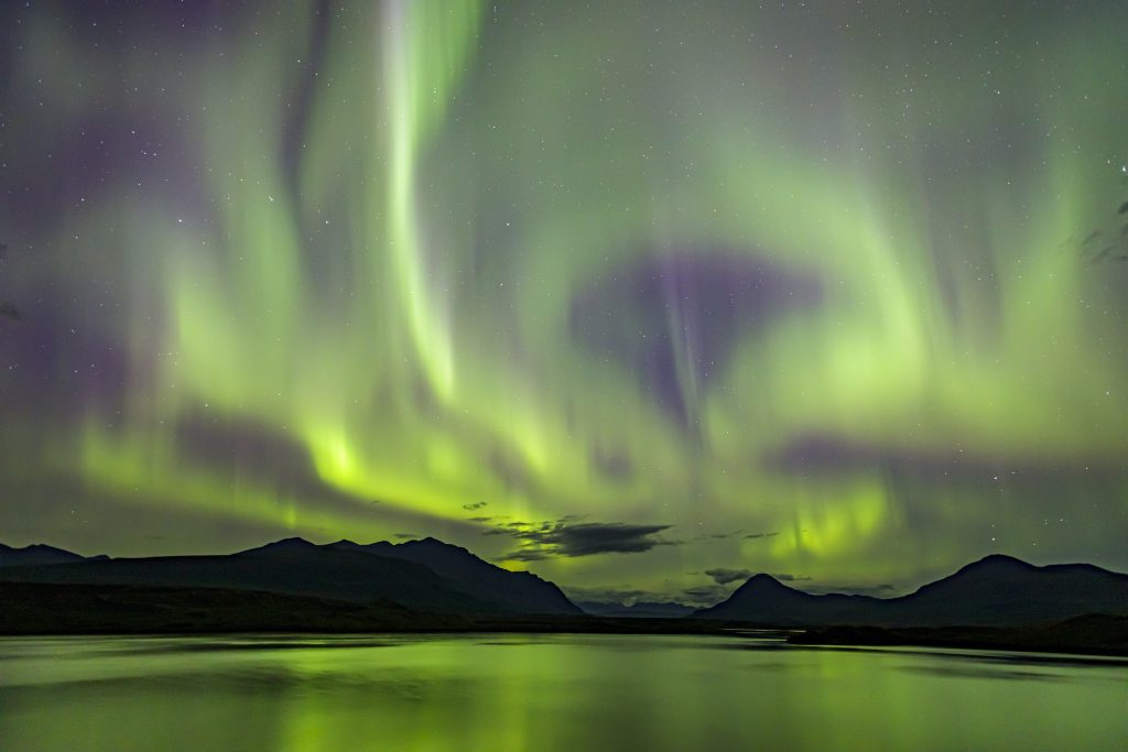 Green aurora swirl over a lake and mountains